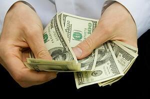 100 dollar bills in a man's hands