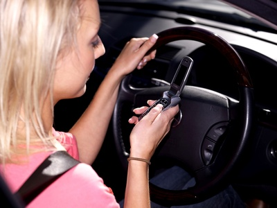 A teenage girl texting while driving.