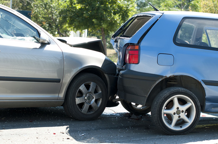 A car accident. The silver car to the left bumped into the back of the blue car to the right.