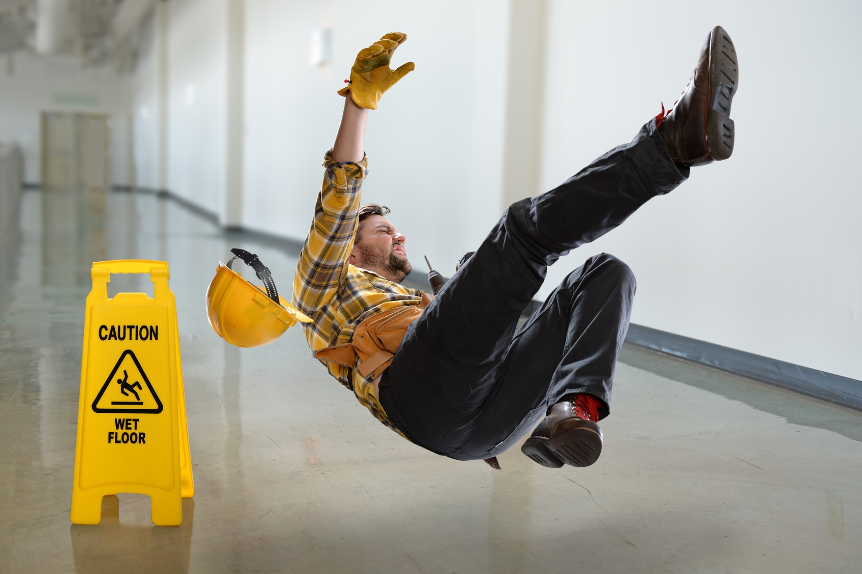 Man slipping and falling on floor with wet floor caution sign
