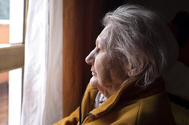 elderly woman alone looking out the window