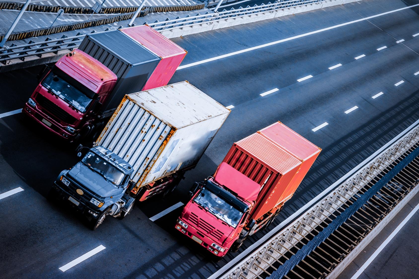three semi trucks on the road