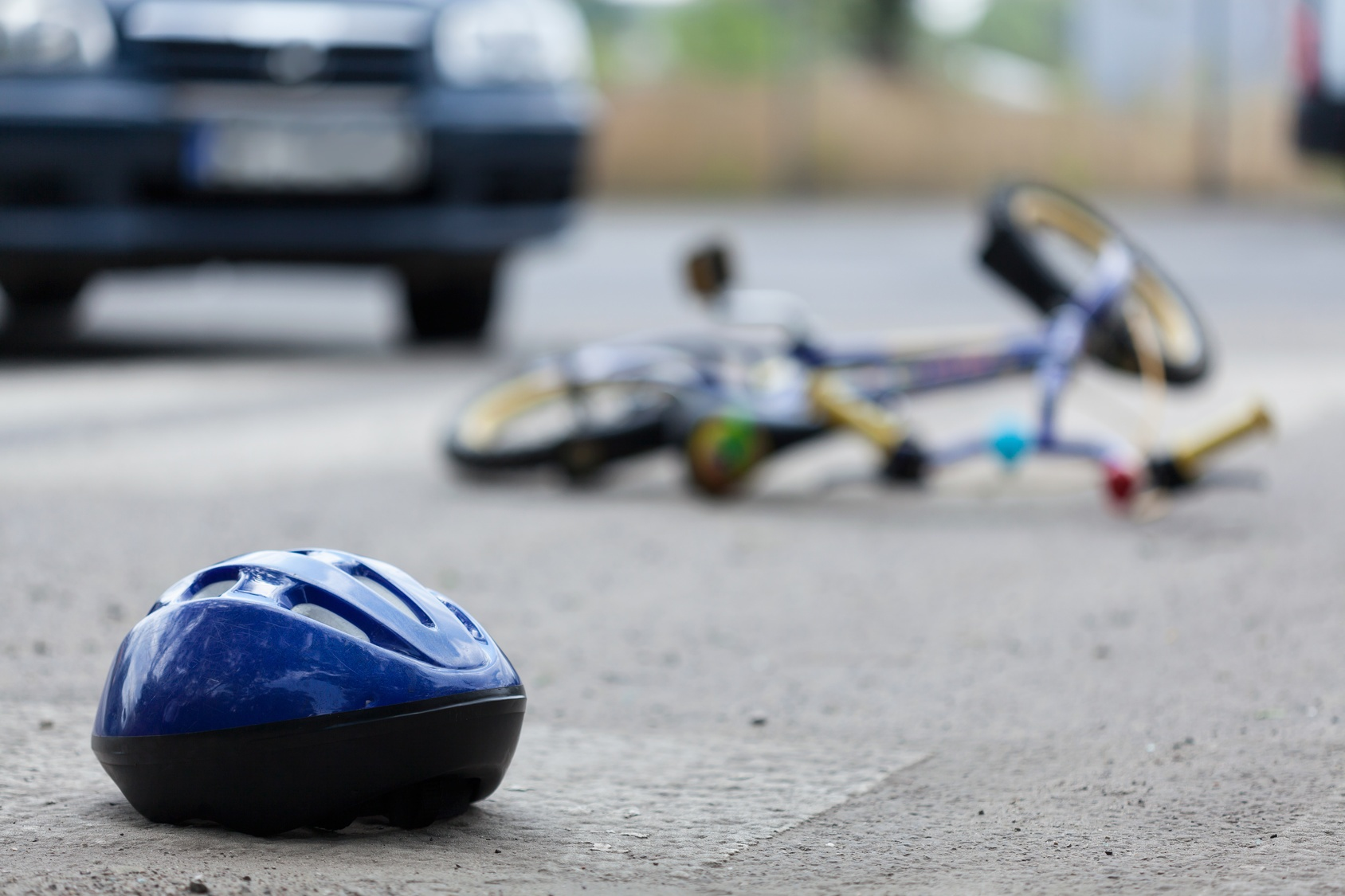 helmet, bicycle and car in the street after a collision