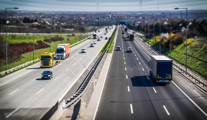 Distant_Highway_with_trucks_and_cars_six_lanes.jpg